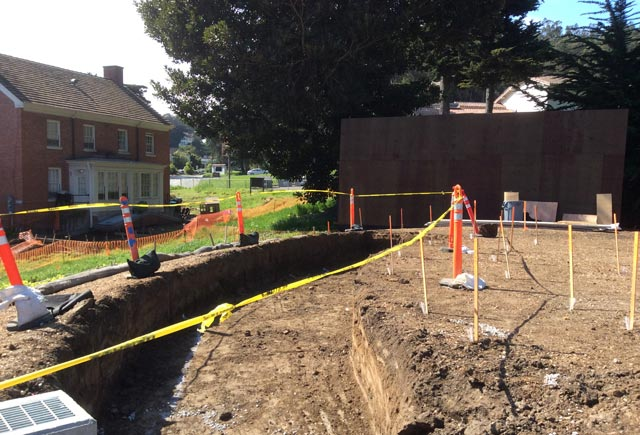 The newly-dug trench with caution tape and orange cones around it at the site.