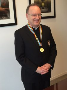 Bishop Barber smiles for photograph while wearing medal