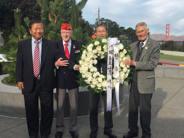 photograph of Deputy Minister Han, Don Reid, John Stevens, and Man J. Kim with wreath at memorial site