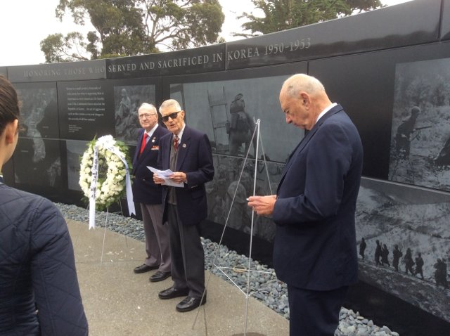 photo of KWMF Treasurer Don Reid, 2nd Vice President John Stevens, and President and Chairman Quentin Kopp speaking in front of memorial wall