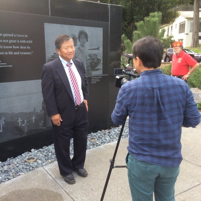 Photograph of Man J. Kim being interviewed for Korean-language television