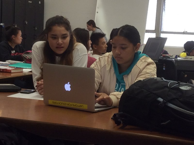 photo of two students working at a computer