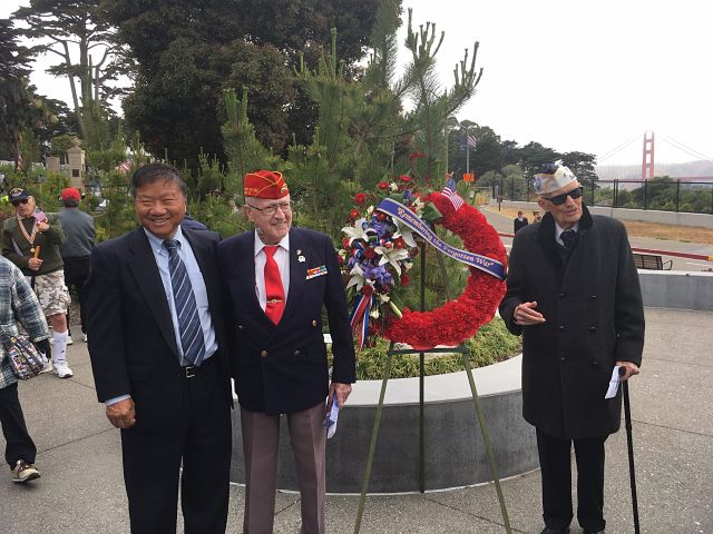 Man J. Kim, Don Reid, and John Stevens with wreath