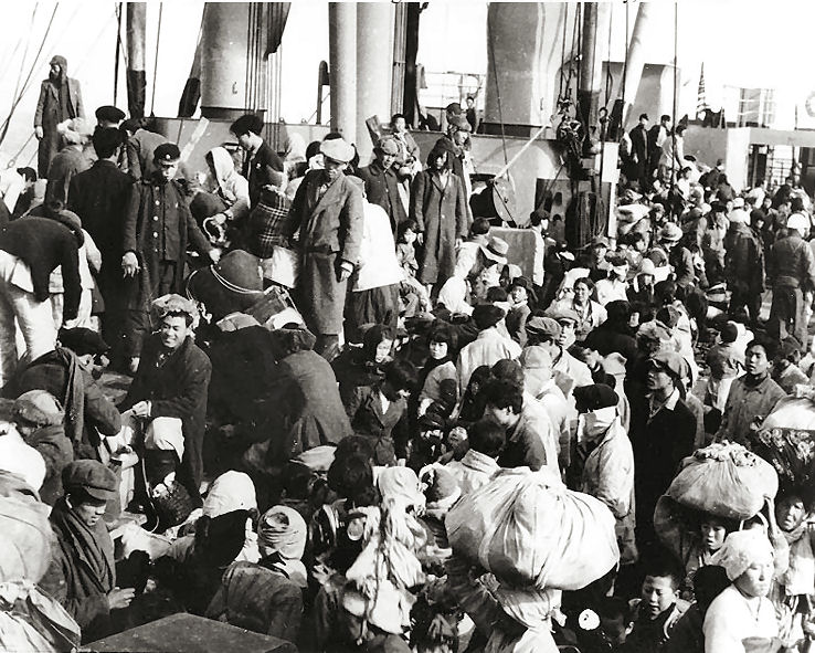 black and white photograph showing refugees crowded on ship deck