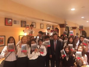 photo of Man J and students with copies of the book