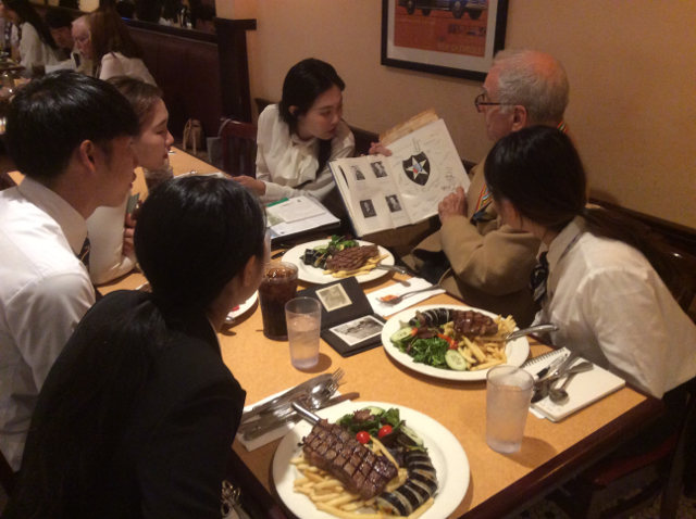 photo of Richard Friedman sharing memorabilia with students over the meal