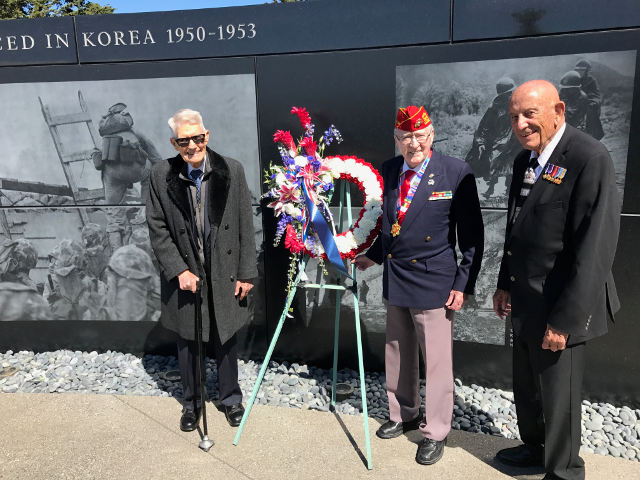 John, Don, and Denny smiling with wreath in front of the wall