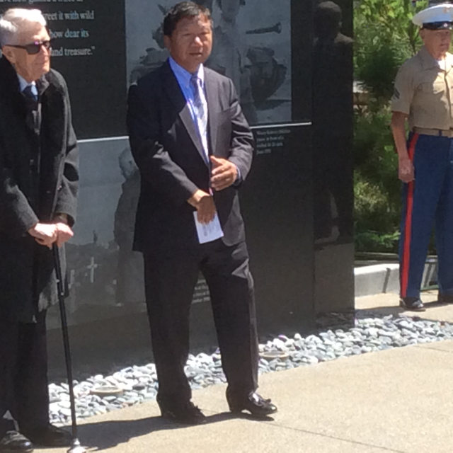 photo of Man J. Kim in front of the wall, speaking