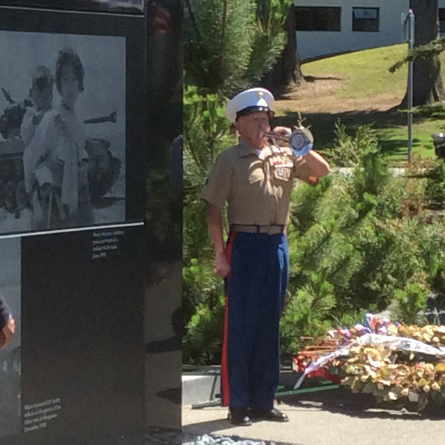 photo of Wally Stewart in Marine uniform playing taps next to the wall