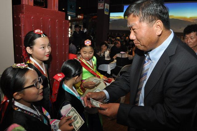 photo of Man J. giving two-dollar bills to kids