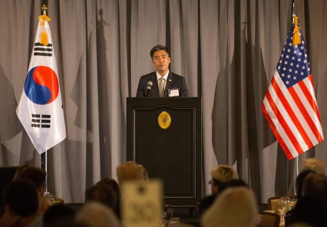 CG Kim at the podium welcoming guests