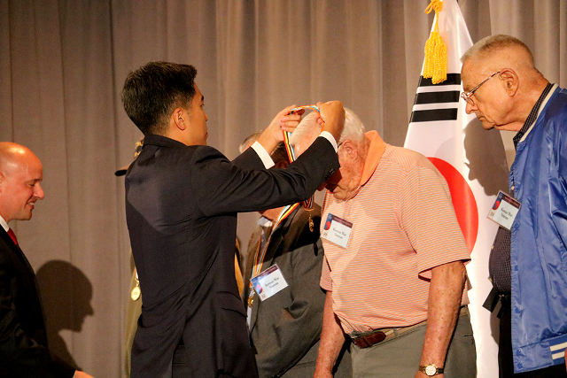 photo of CG Kim putting a medal on a veteran