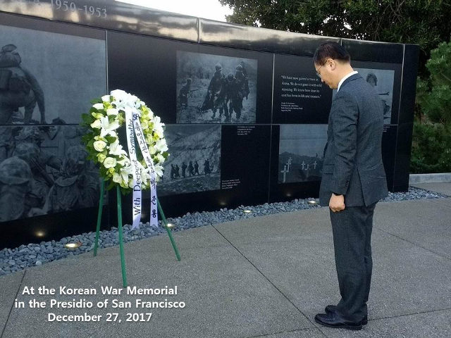 photo of CG park with head bowed at memorial
