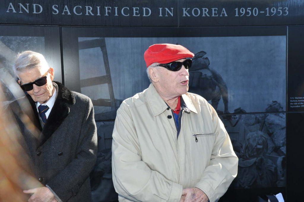 photo of Des standing in front of memorial, speaking