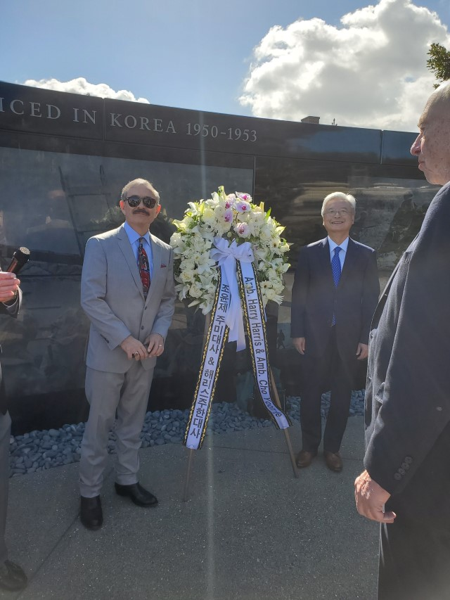 the two ambassadors stand with the wreath at the Memorial wall