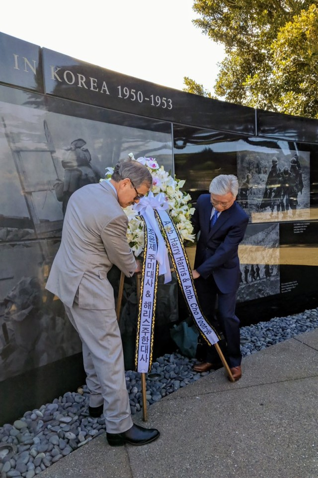 the two ambassadors place the wreath at the Memorial wall