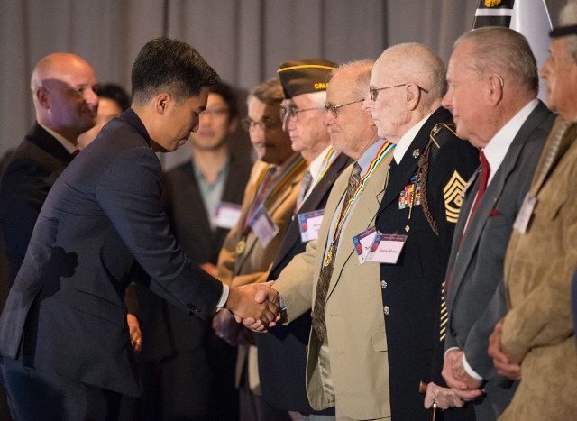photo of Consul General Jimin Kim shaking hands with a line of veterans