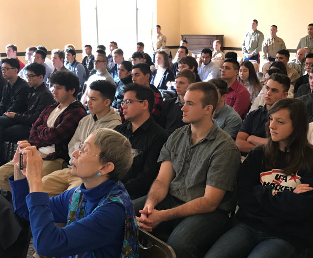 photo of seated audience listening to speakers