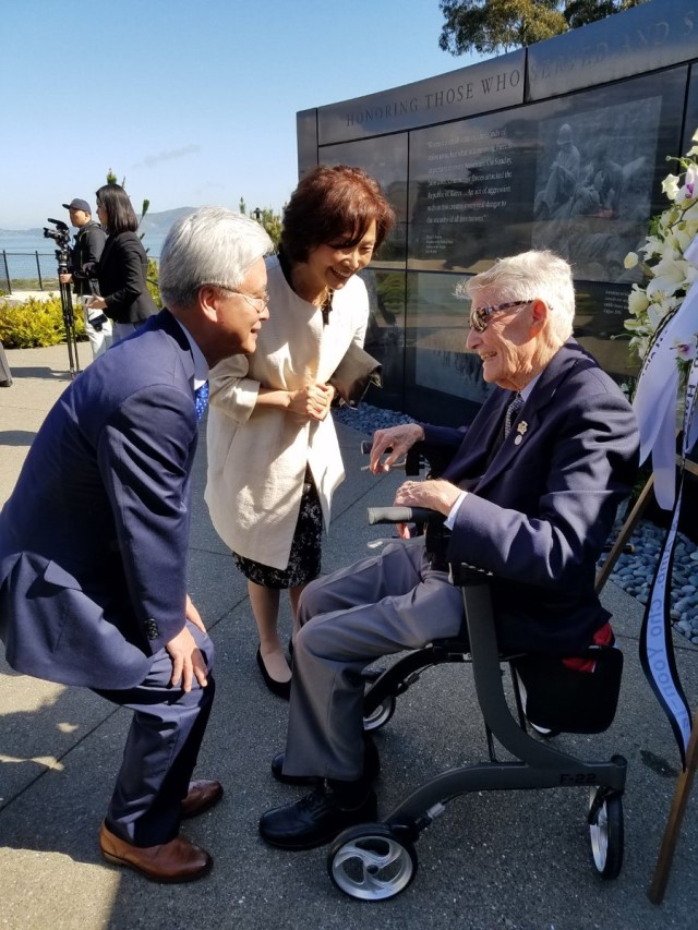 Ambassador and Mrs. Cho speak with John Stevens near the Memorial wall