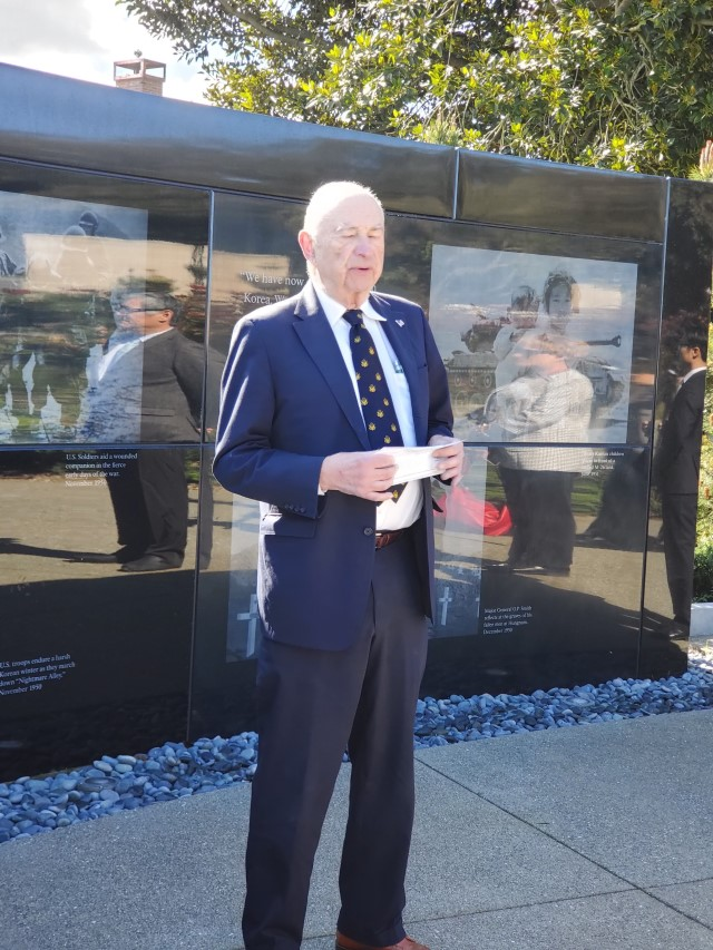 Quentin Kopp speaks in front of Memorial wall