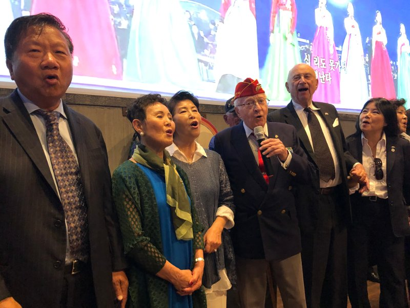 a larger group sings Arirang